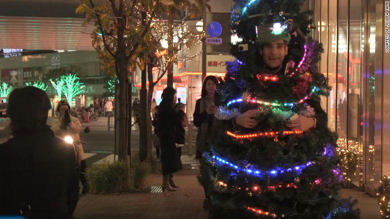 Hombre disfrazado de árbol difunde el espíritu navideño por las calles de Tokio