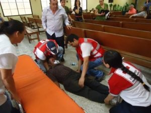 Los jóvenes de la Cruz Roja atienden a un señor epiléptico dentro de una iglesia.
