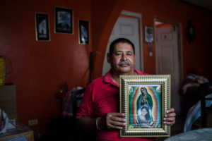 Jesús René Maradiaga, un líder de la comunidad, sostiene una imagen de la Virgen de Guadalupe con un retrato de su hija, Yury Tatiana Maradiaga, que fue asesinada en 2005. Credit Katie Orlinsky para The New York Times
