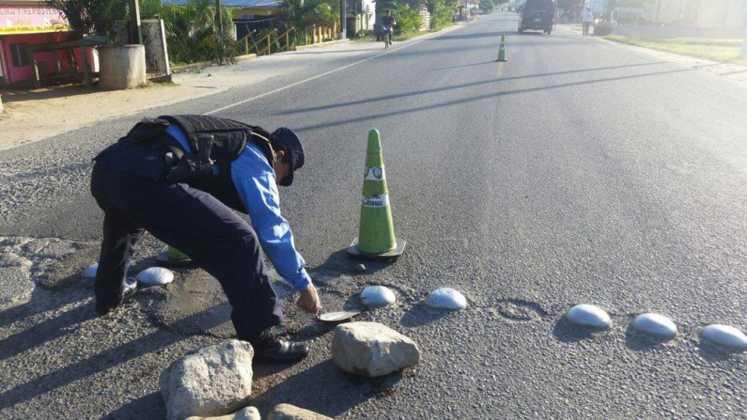 Un agente policial repara baches en Atlántida.