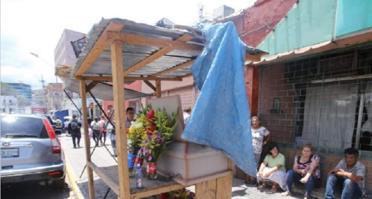 Madre de escasos recursos vela a joven en plena calle; supuestamente murió por dengue