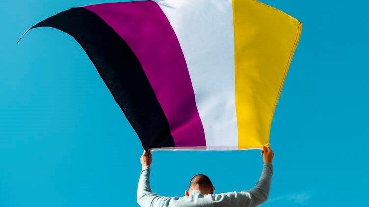 person waving a non-binary pride flag