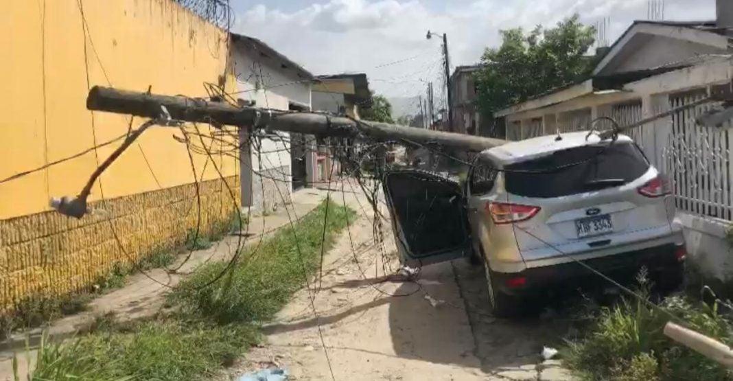Poste de tendido eléctrico cae en carro