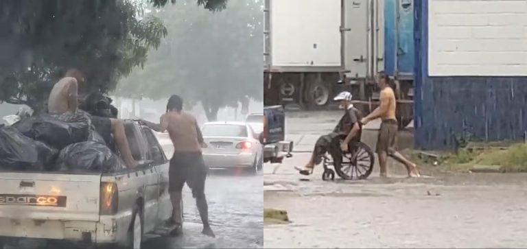 Bajo la lluvia, hondureño ayuda a persona en silla de ruedas a cruzar calle inundada