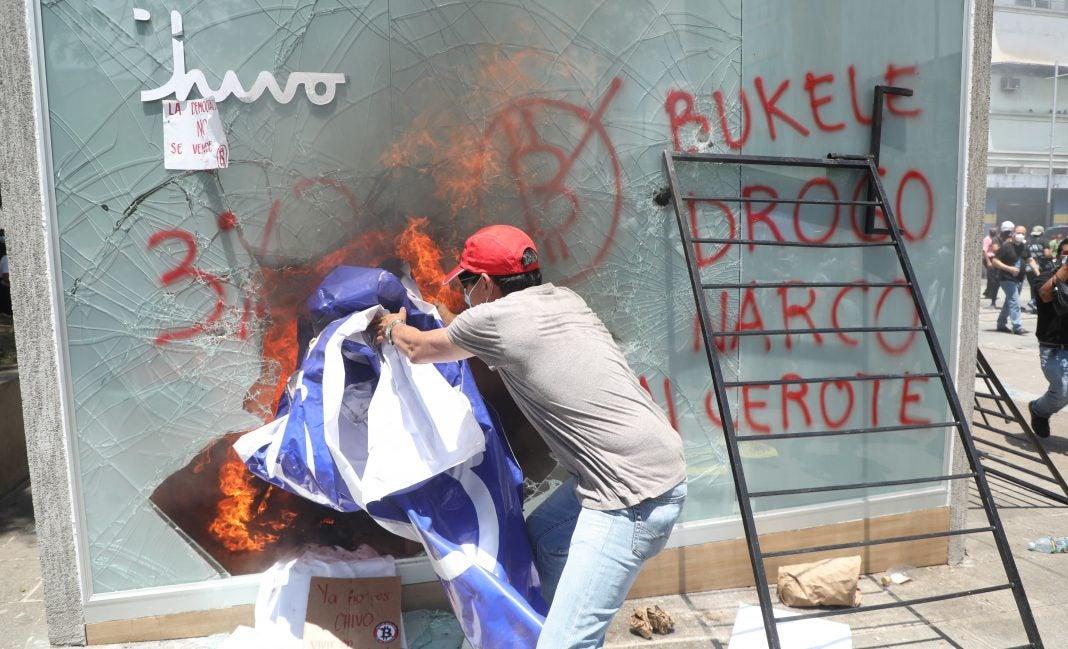 Un manifestante destroza un cajero automático bitcoin de Chivo Wallet durante una protesta.