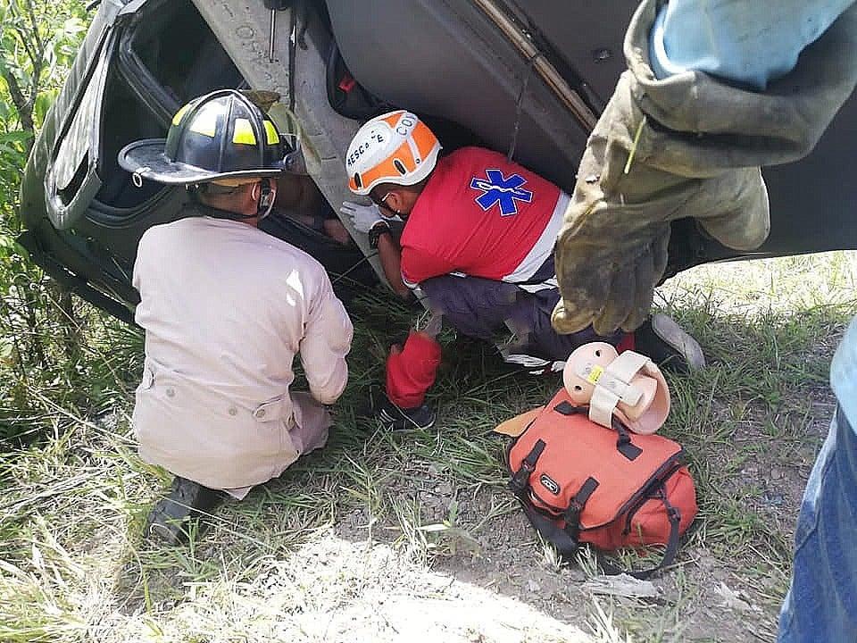 Los bomberos tratan de rescatar al conductor que falleció.